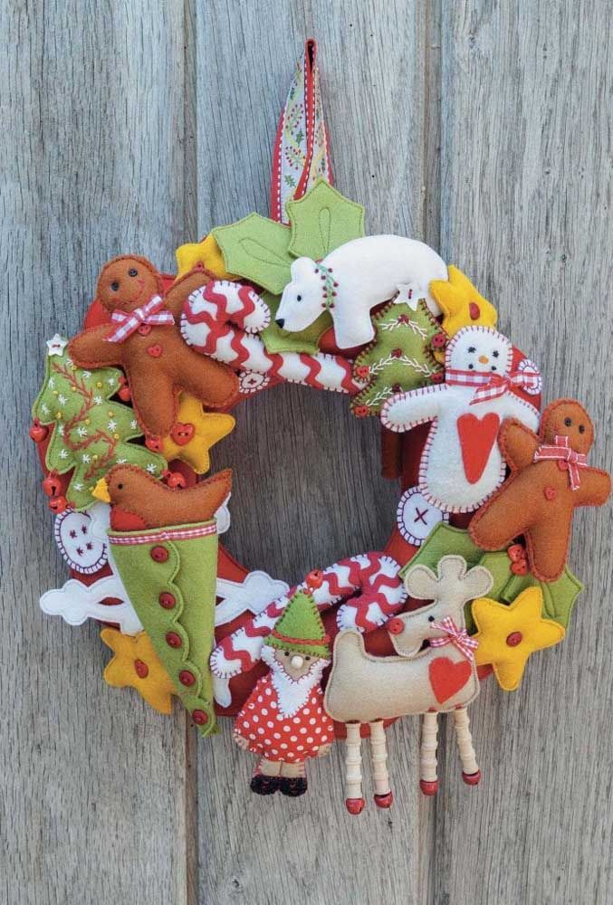 uma guirlanda repleta de motivos natalinos, entre eles, papai noel, renas e bonecos de neve.