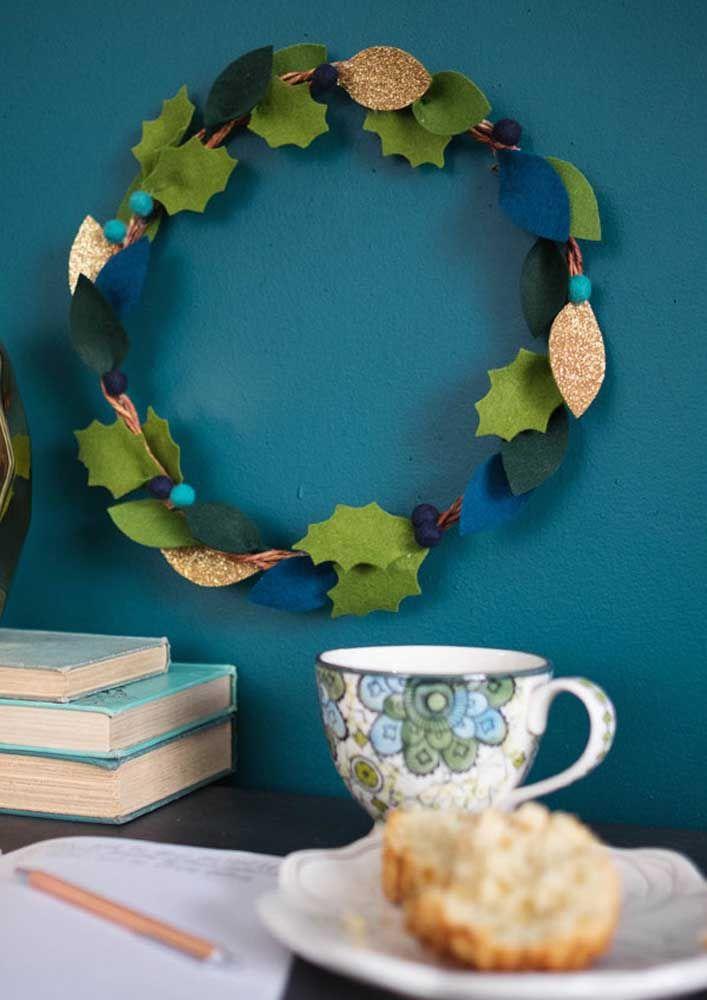 A guirlanda verde de feltro cai como uma luva sobre a parede azul