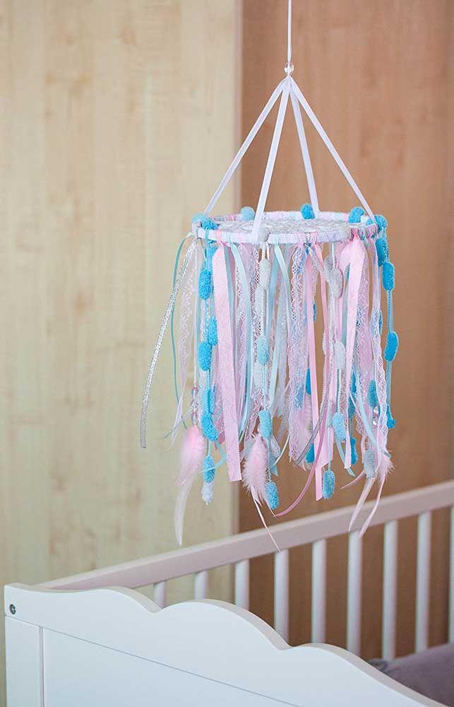 Móbile em forma de filtros dos sonhos com pompons e fitas para o berço do bebê