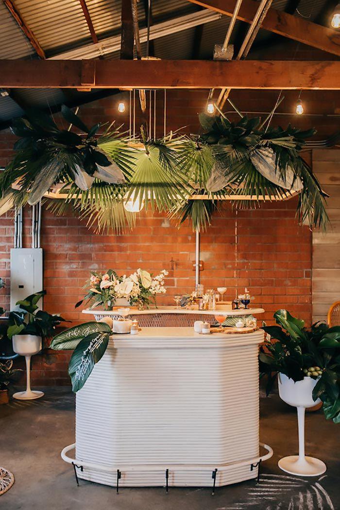 Nessa imagem, as folhas de palmeira azul foram usadas para decorar o bar rústico e aconchegante