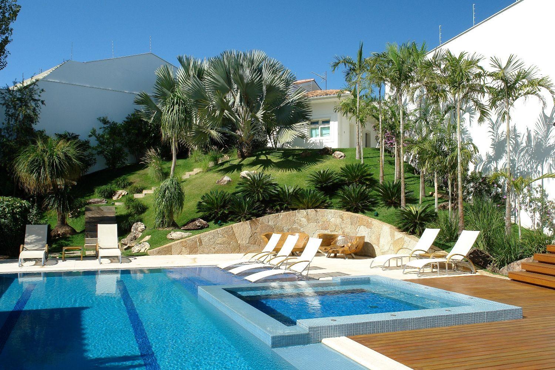 Aqui, a palmeira azul foi plantada bem no centro do jardim escondendo atrás dela uma delicada casinha branca