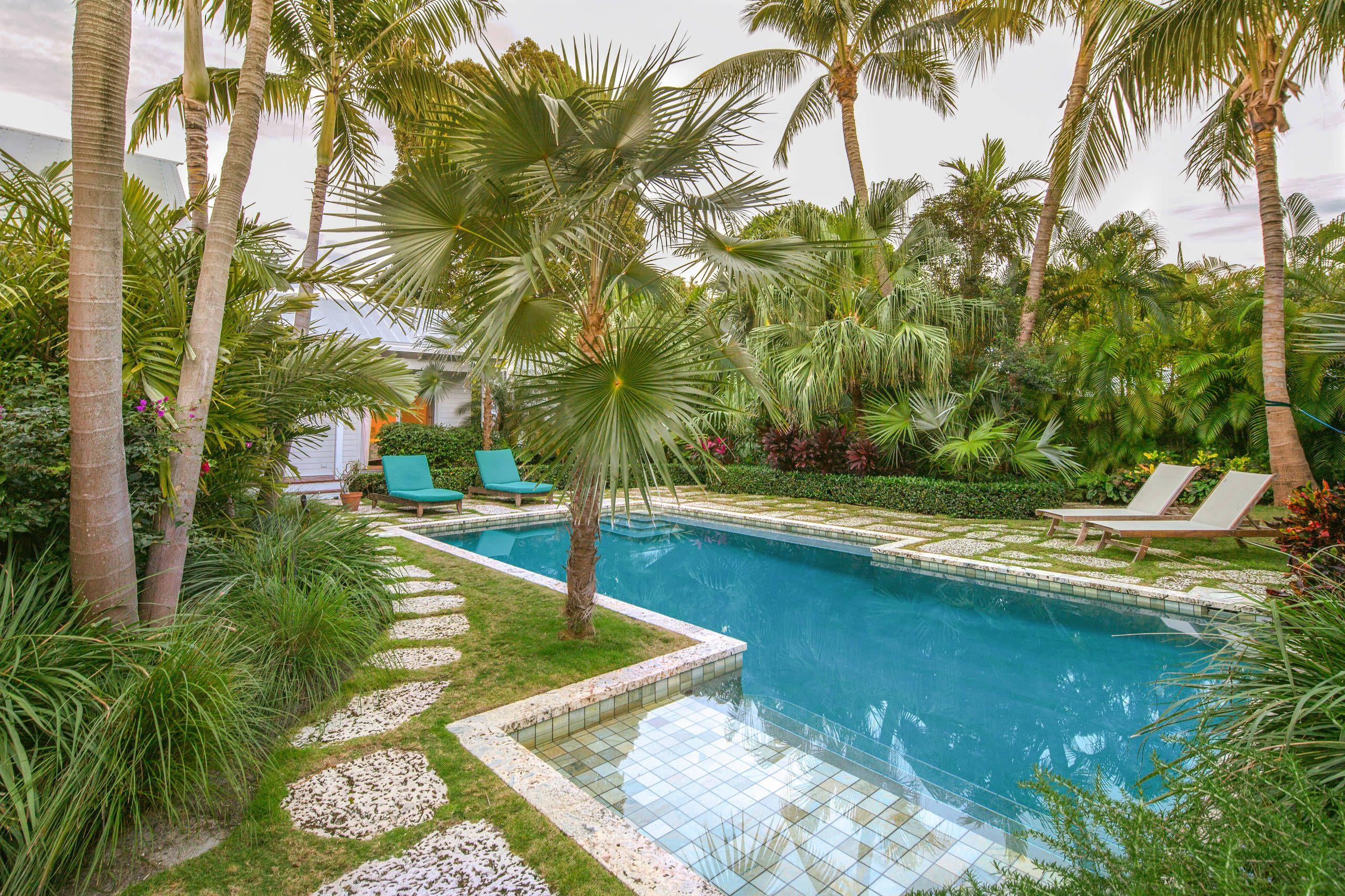 A piscina dessa casa foi cercada por plantas tropicais, entre elas a palmeira azul, formando um jardim exuberante