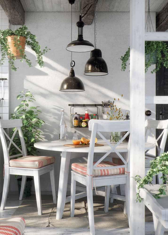 A pátina branca, ou provençal, foi a escolhida para dar o acabamento na mesa, nas cadeiras e no batente da porta; mais ao fundo, a porta escura também recebeu o aspecto envelhecido da pátina