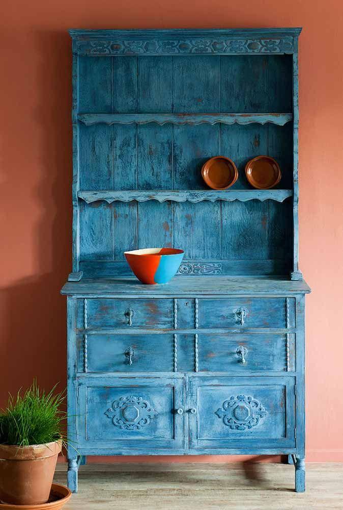 A parede de tom damasco realça o azul alaranjado da pátina dessa cristaleira