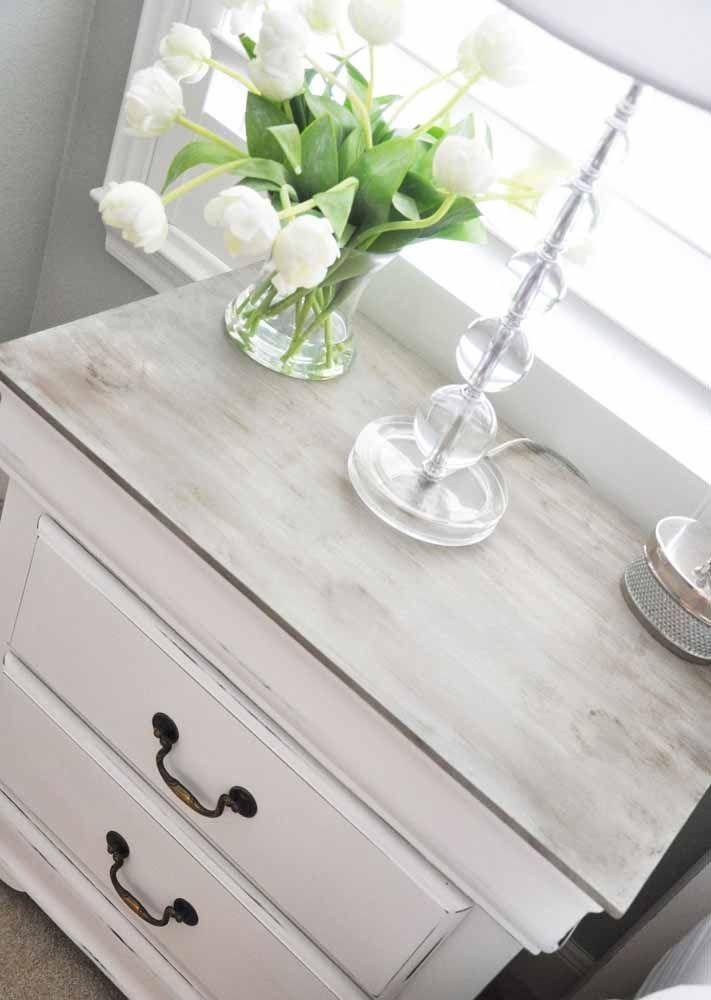 Criado-mudo em pátina branca; destaque para o fundo amadeirado do móvel