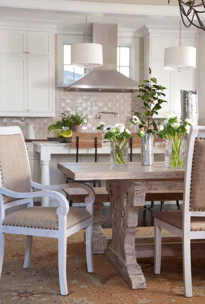 A mesa de madeira maciça ganhou a companhia de cadeiras com pátina branca