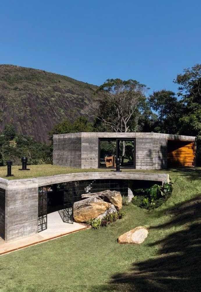 Essa casa parece se camuflar em meio às montanhas e à vegetação