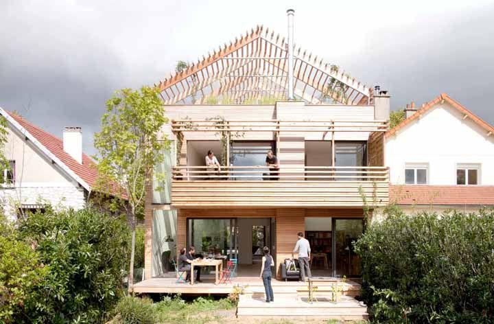 Sobre o telhado verde, uma estrutura vazada de madeira que imita um telhado de duas águas; um efeito bonito e diferente