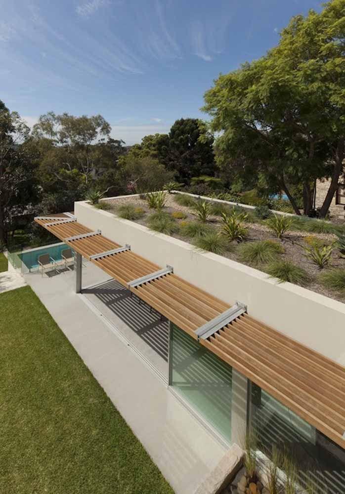 A casa de formato retangular apostou em um telhado verde com touceiras de plantas bem espaçadas uma da outra