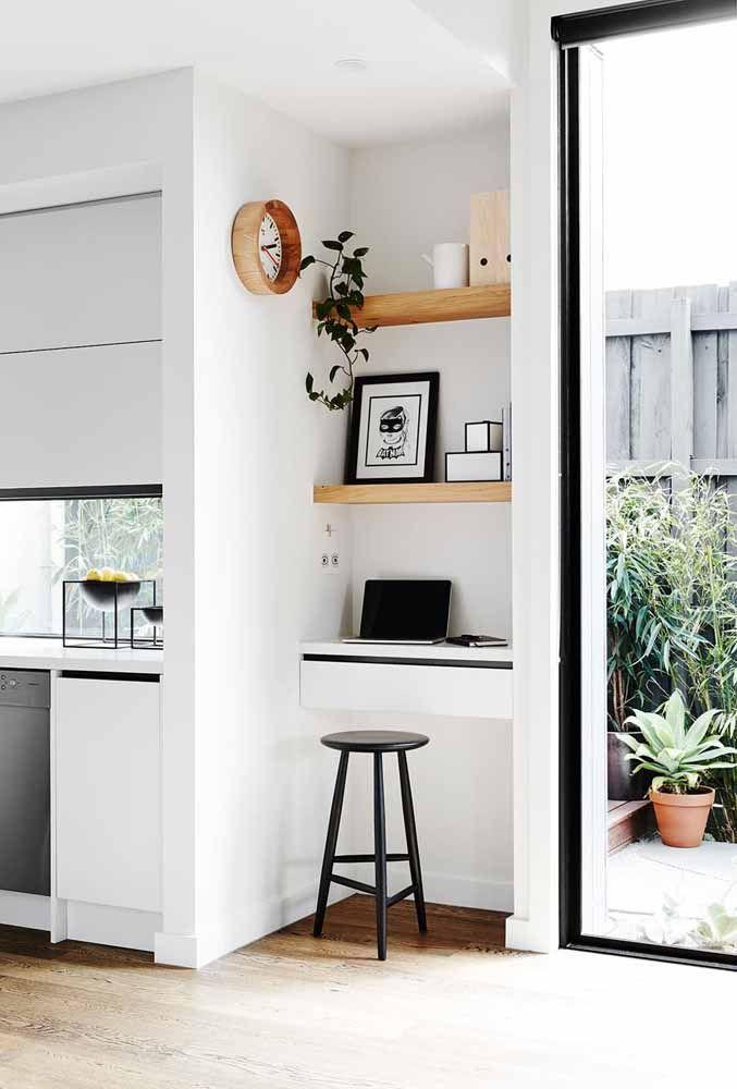 Escrivaninha suspensa branca com prateleiras de madeira posicionada em um local estratégico da casa