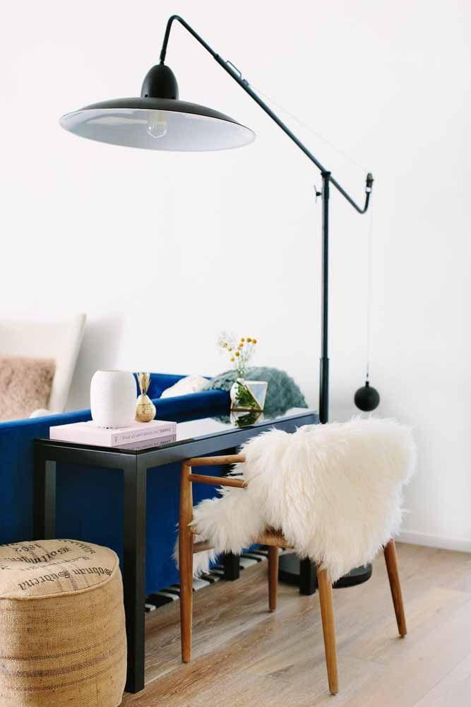 A escrivaninha aqui fica na sala, mas em um espaço planejado para ela com direito até a uma luminária bem destacada