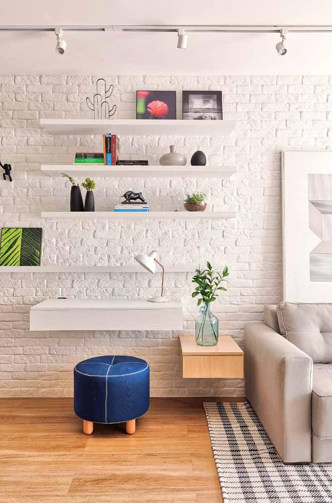 A parede de tijolinhos dessa sala recebeu a escrivaninha suspensa e as prateleiras brancas com muito charme