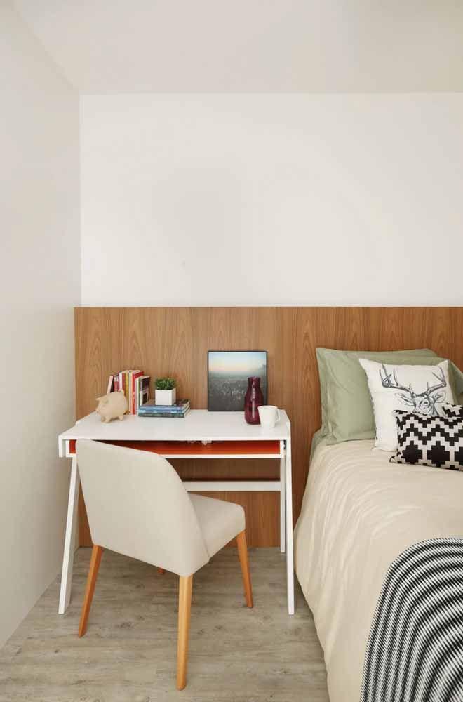 Nesse quarto, a cabeceira da cama funciona como um complemento da escrivaninha pequena