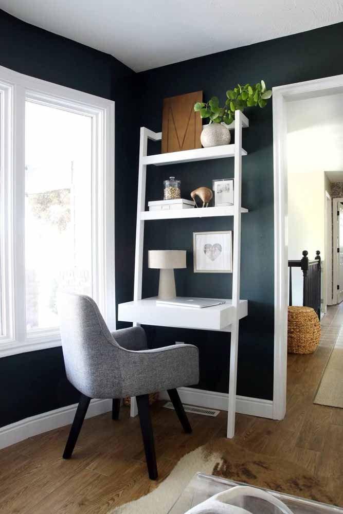 A escrivaninha pequena branca é simples, mas a poltrona que a acompanha é puro conforto; sem contar a parede azul que deixa o móvel ainda mais em evidência