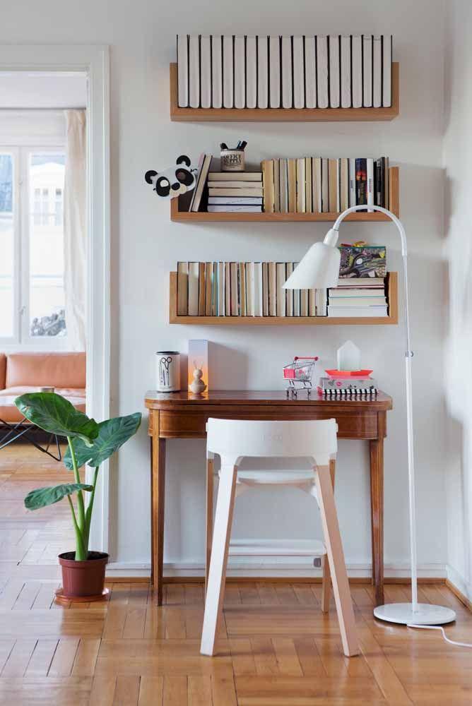 A escrivaninha de madeira combina perfeitamente com o assoalho; o vaso com folhagem ajuda a destacar o espaço da escrivaninha pequena no ambiente