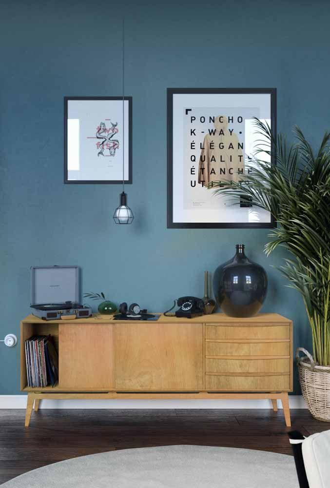 Em frente à parede azul, o rack retrô de madeira exibe com muito orgulho um antigo telefone, uma vitrola e discos de vinil