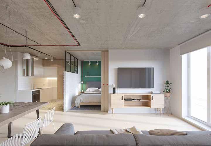Essa casa de estilo industrial investiu em um rack retrô para decorar a sala; destaque para os pés trabalhados do móvel