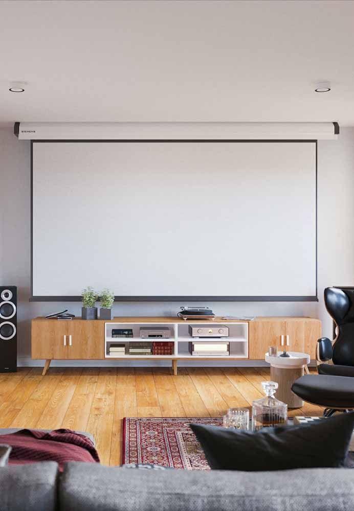 Nessa sala moderna, não é só o rack que é retrô; os objetos sobre ele também são puro saudosismo, entre eles a vitrola e o vídeo cassete