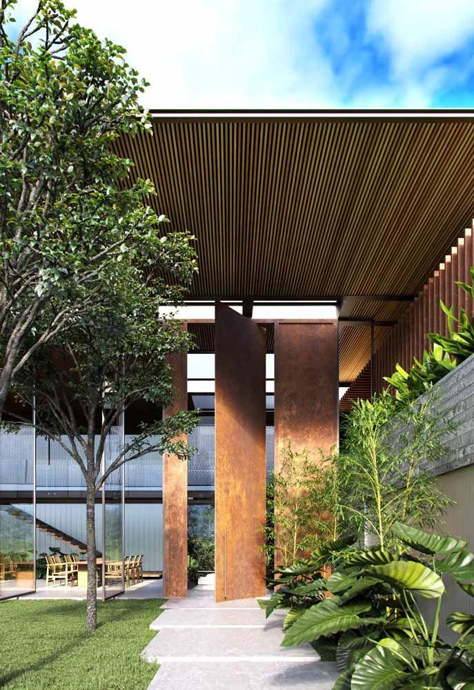As placas de aço corten dessa fachada funcionam como revestimento e porta de entrada