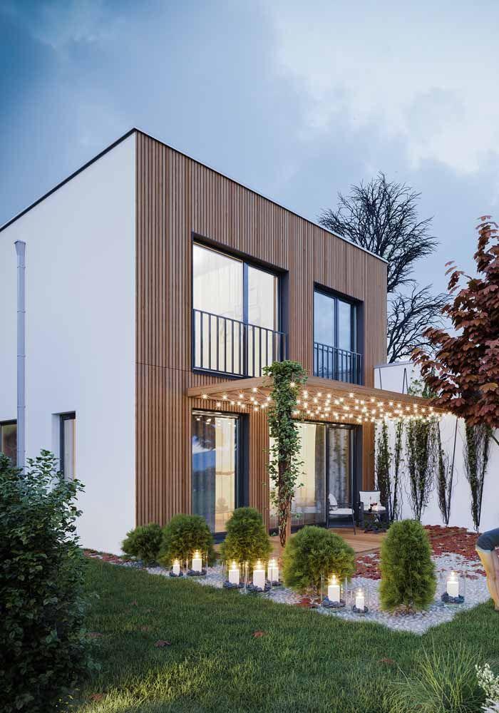 A fachada de madeira realçou a proposta acolhedora e receptiva da casa; destaque para o pergolado também de madeira e decorado com lâmpadas