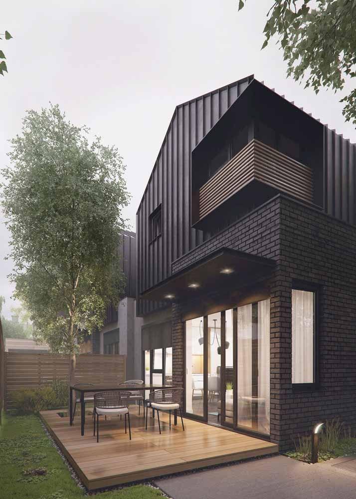 A proposta aqui foi mesclar tijolos com chapas de aço; a madeira no deck de entrada dá uma aparência mais suave ao projeto