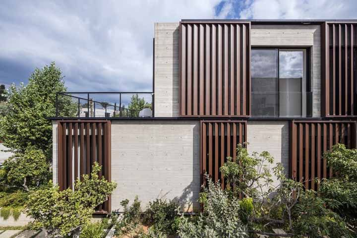 Dá para deixar a fachada acolhedora mesmo sendo de concreto, para isso invista na combinação do material com a madeira
