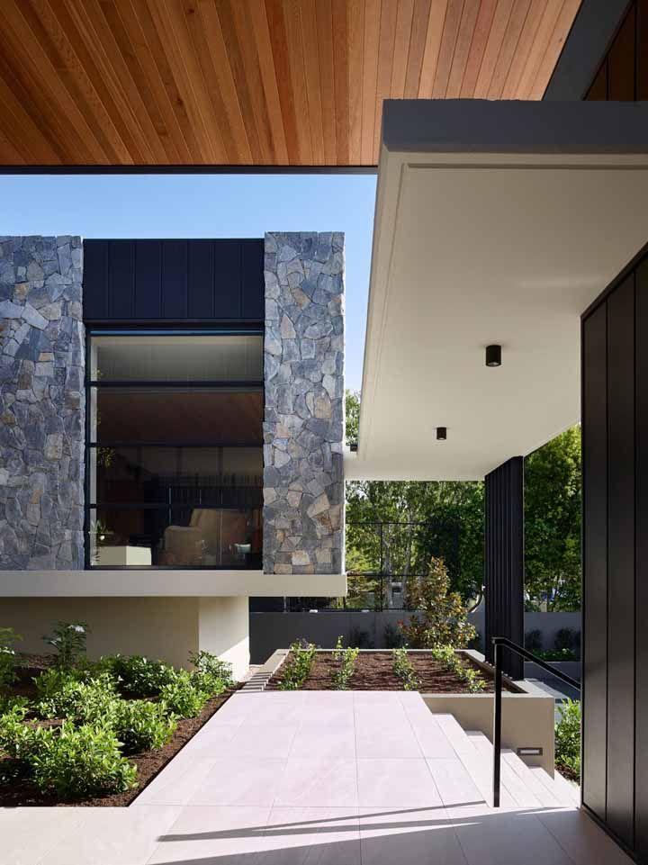 Pedras cinzas em estado bruto tomam conta da parede externa dessa casa