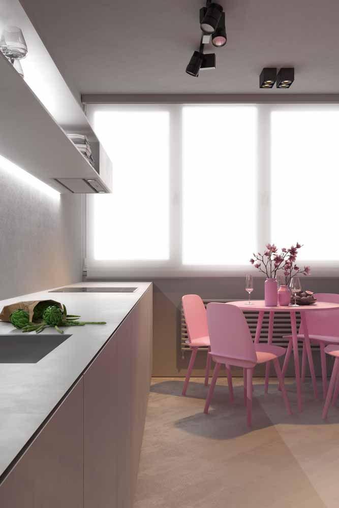 A mesa e as cadeiras cor de rosa tinham tudo para se tornarem móveis da cozinha da Barbie, mas a frieza e a sobriedade do armário cinza inviabilizaram a ideia
