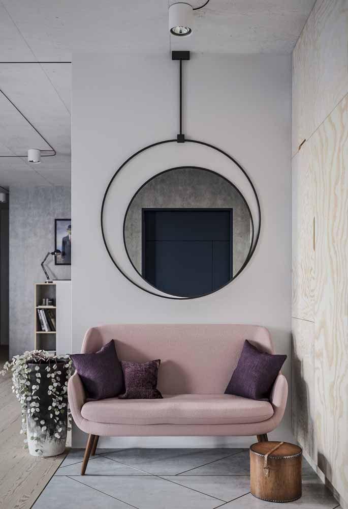 Sofá cor de rosa; para quebrar a atmosfera romântica da cor a opção foi usar almofadas roxas e um espelho com moldura preta