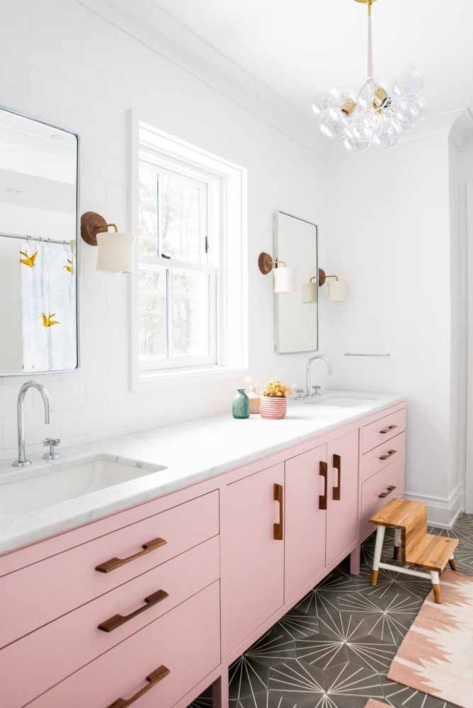 Um luxo essa cozinha de armários cor de rosa, puxadores de madeira e bancada de mármore branco, sem falar do piso preto no chão