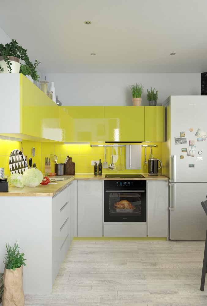 Branco e amarelo na cozinha: uma composição clean e equilibrada valorizada pelo verde das plantas