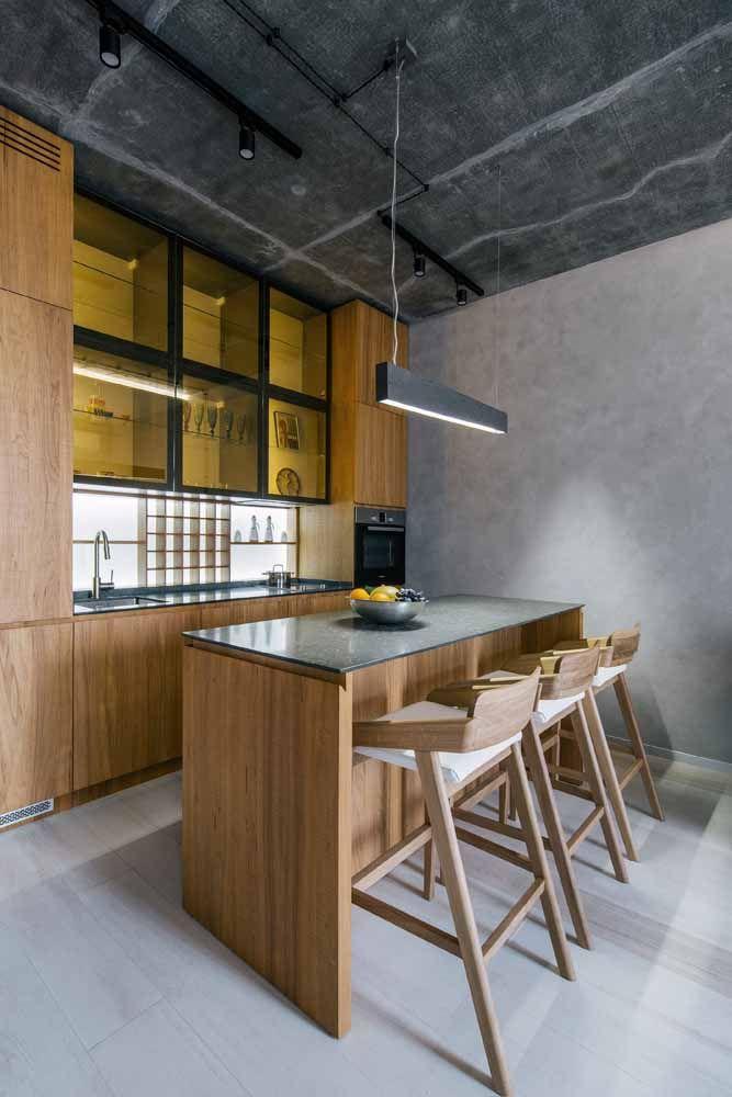 A combinação entre amarelo e o tom amadeirado dos móveis deixa a cozinha aconchegante; o preto e o cinza estão lá para lembrar que a proposta, no entanto, é industrial