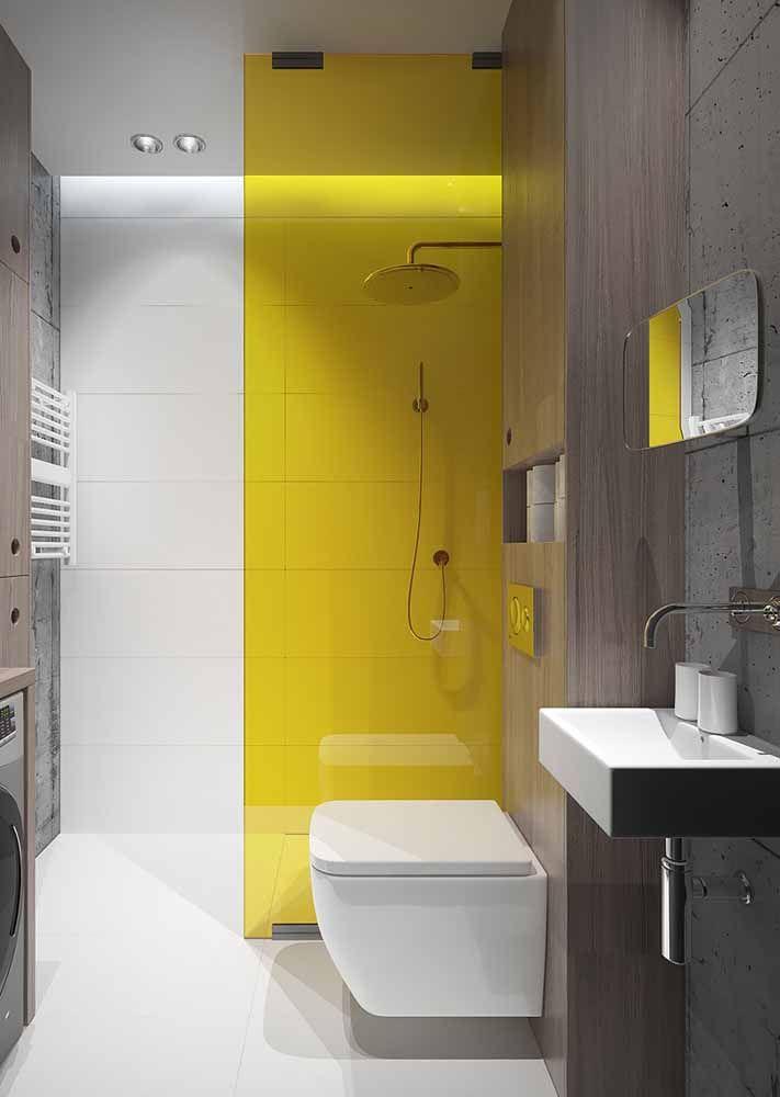 E o que acha de causar um efeito visual no banheiro? Aqui, a divisória de vidro causa a sensação de que a parede é amarela