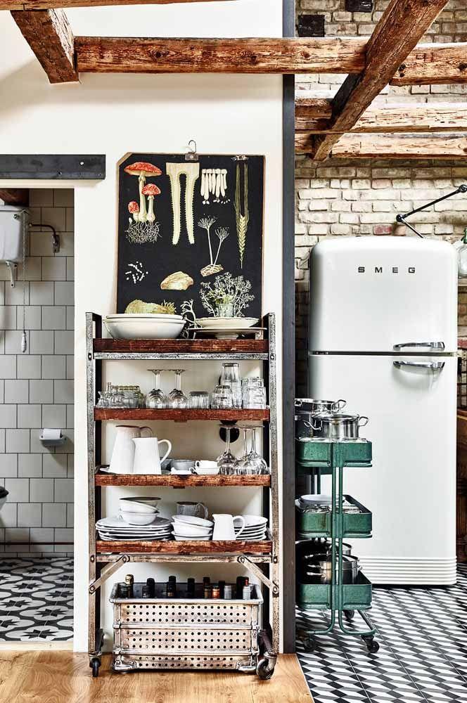 O carrinho de metal organiza e expõe as louças dessa cozinha retrô marcada pela combinação entre o preto e o branco
