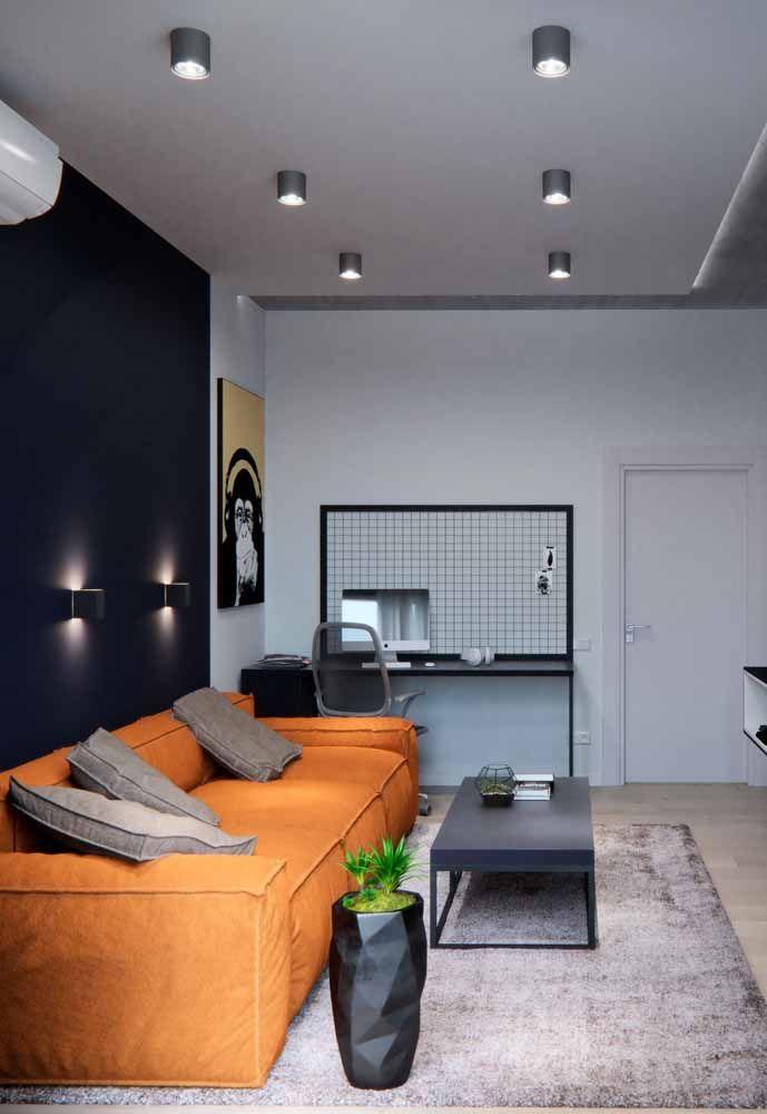 Nessa sala, o sofá laranja se destaca