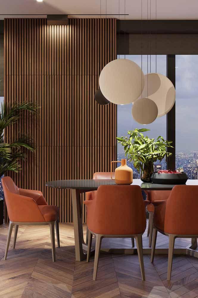 Cadeiras na cor laranja se destacam nessa sala de jantar