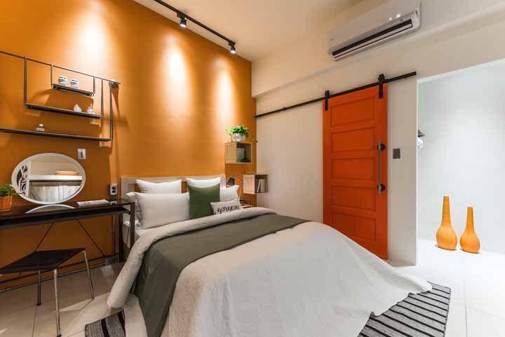 Nesse quarto de casal, a parede laranja se destaca ainda mais em função da iluminação