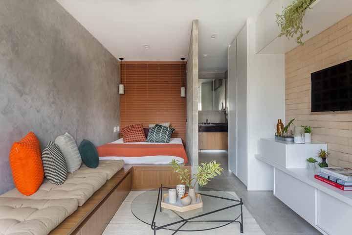 Em ambiente Studio, este apartamento usa o laranja na cama de casal e nas almofadas para a sala