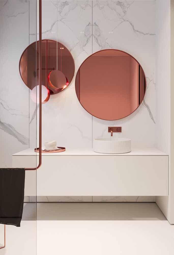 Banheiro para esbanjar sofisticação: a parede de mármore branco foi valorizada com os detalhes em Rose Gold.