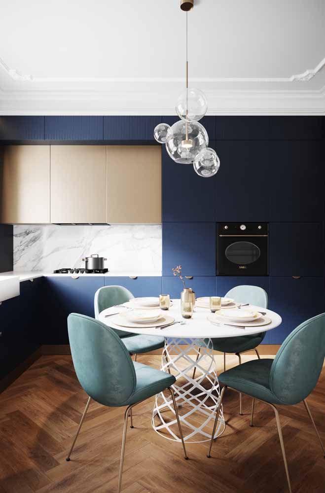 O azul marinho combinado com o tom pastel amarelado fica perfeito na escolha de cores deste armário de cozinha planejado