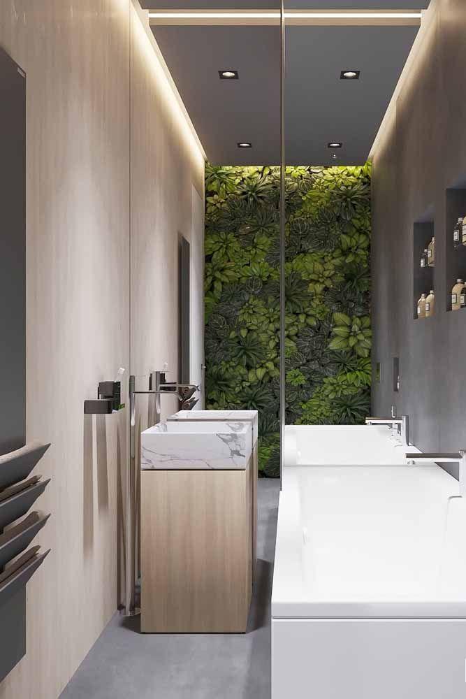 Em um ambiente neutro de banheiro, a parede de plantas chama a atenção pelos tons de verde