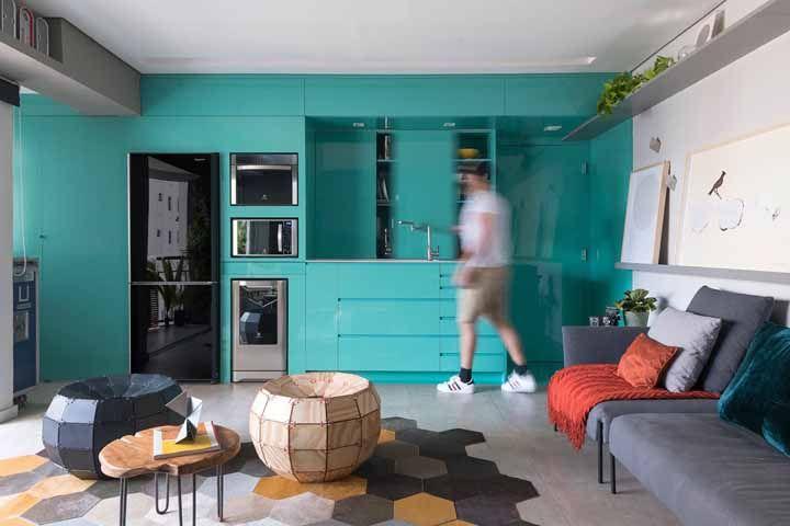 Cozinha como um paredão azul turquesa neste espaço conjugado com a sala