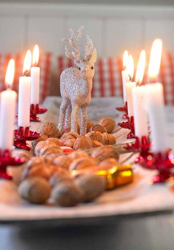 Decoração de centro de mesa com nozes, velinhas e uma rena pronta para celebrar as festas