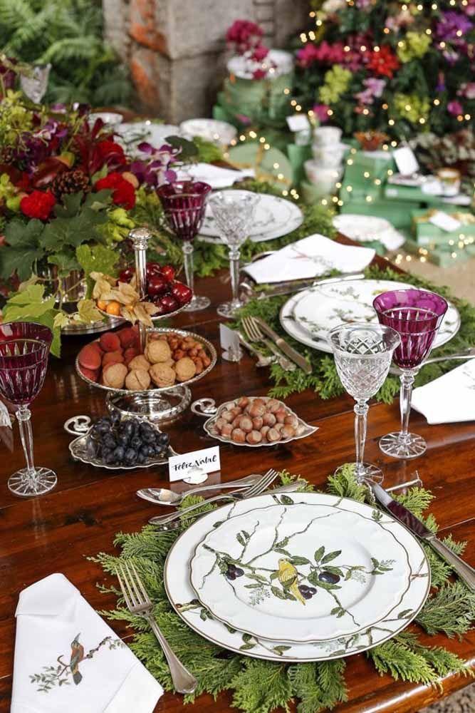 Folhas de pinheiro fazendo o papel do jogo americano nesta decoração de mesa de Natal