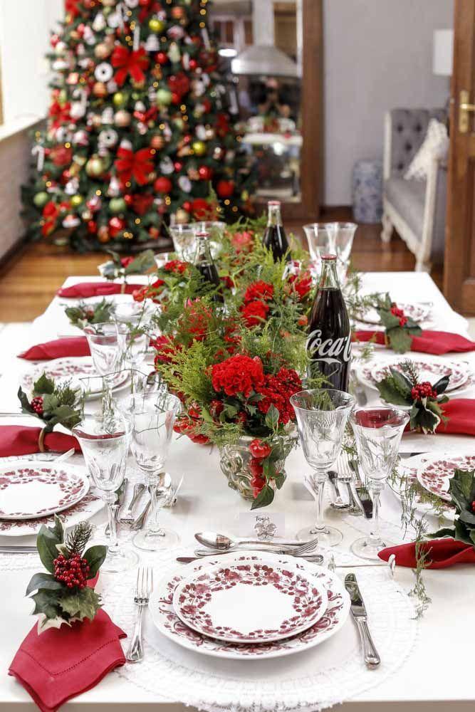Arranjos de flores vermelhas e folhas verdinhas como centro de mesa desta ceia de Natal