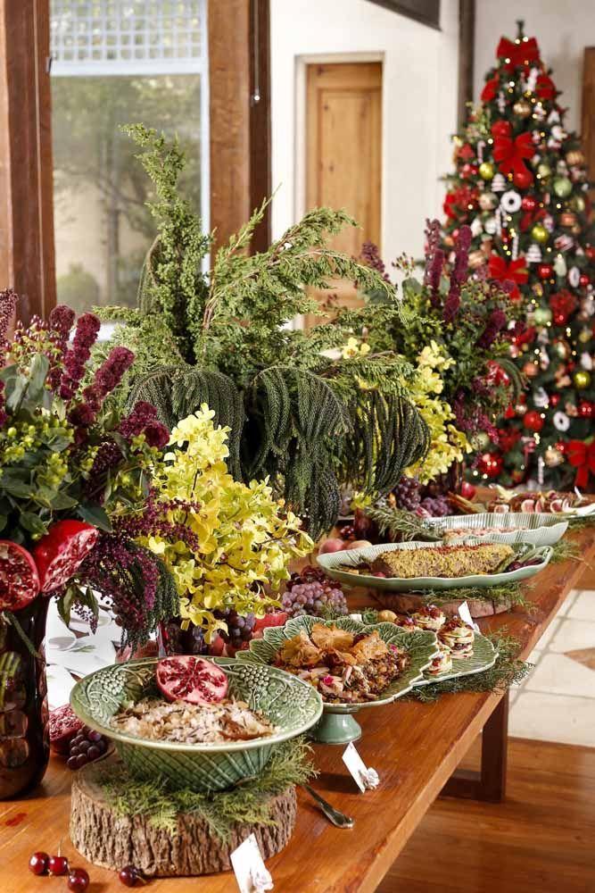 As frutas da estação vão completando os espaços deixados pelos arranjos neste outro exemplo de mesa de Natal florida