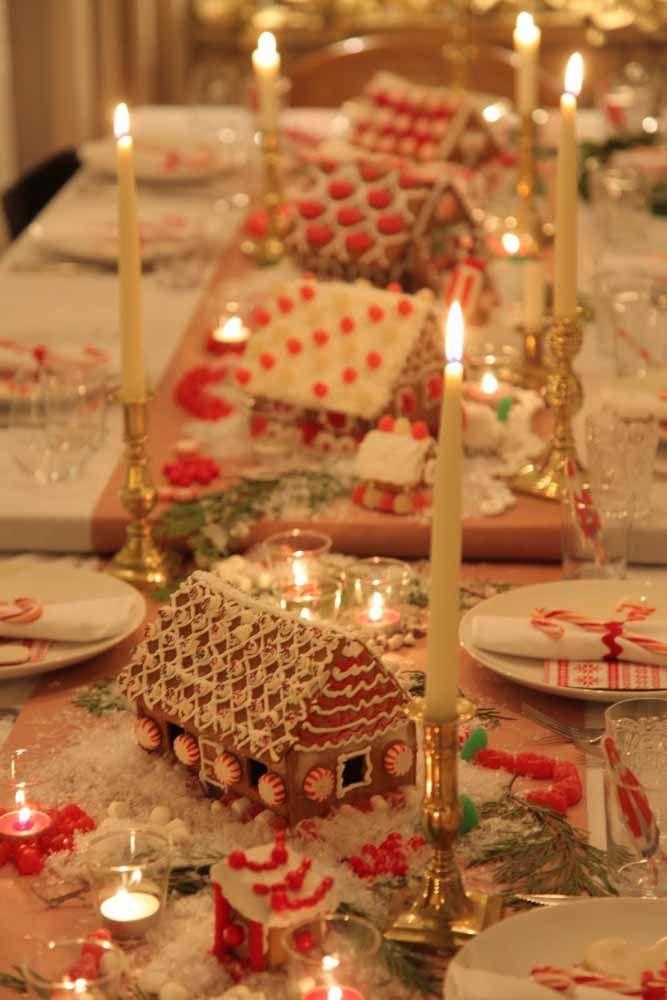 Vila natalina como o centro desta mesa de Natal com casinhas-biscoitos de gengibre com glacê