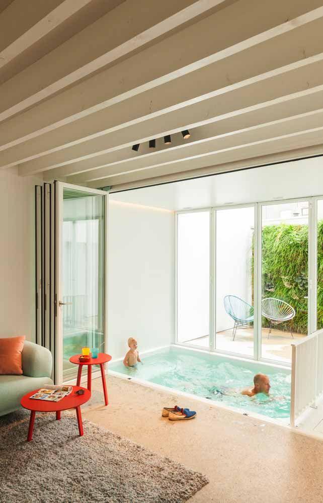 A solução para isolar a piscina da sala foi a porta sanfonada de vidro