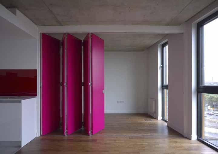 O ambiente neutro não poderia ficar mais ousado do que com essa porta sanfonada rosa choque
