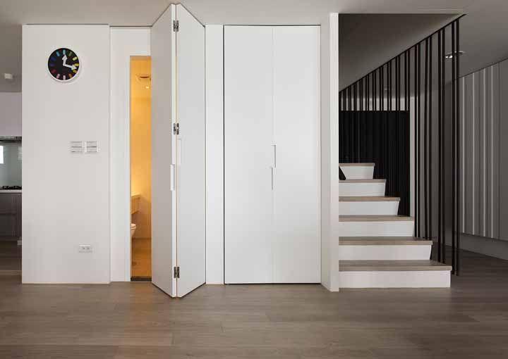 Branca por fora, amarela por dentro: a porta sanfonada permite esse jogo de contrastes e surpresas